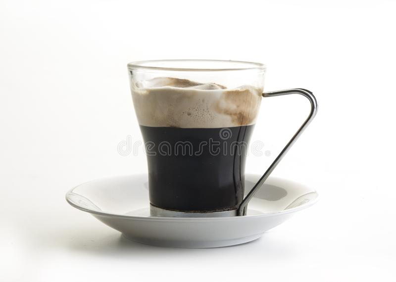 Glass cup with cappuccino coffee inside, seen frontally. Glass cup with cappuccino coffee inside viewed frontally and on a white background royalty free stock photos
