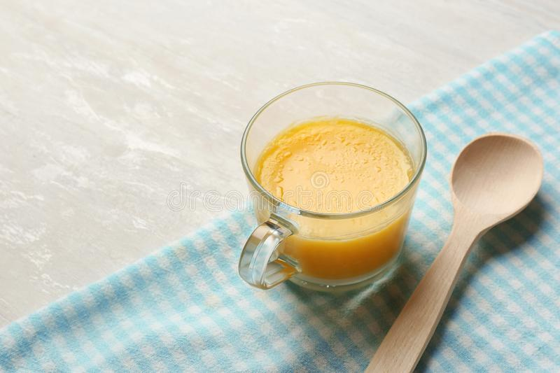 Glass cup with clarified butter and wooden spoon on table. Space for text stock photography
