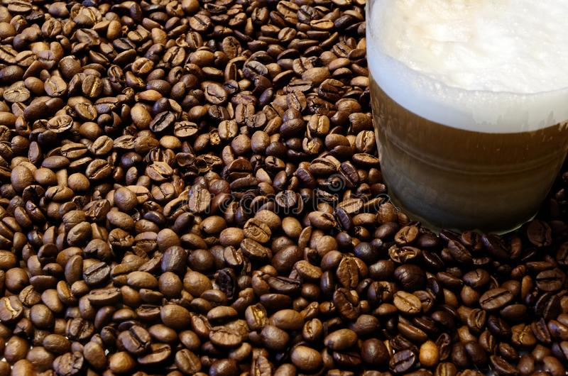 Roasted coffee beans and a cup of coffee. Glass cup of coffee in roasterd coffee beans as background stock photo