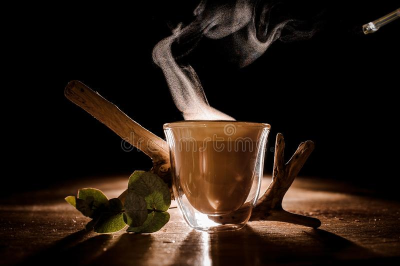 Glass cup of coffee with steam from it. Near plant decor located on the wooden table royalty free stock image