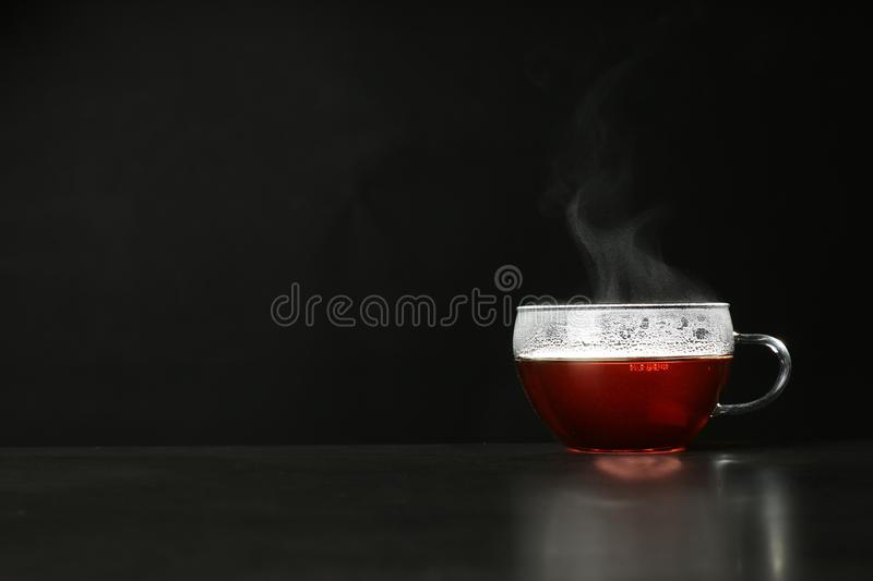 Glass cup with delicious hot tea on table against dark background. Space for text stock photography