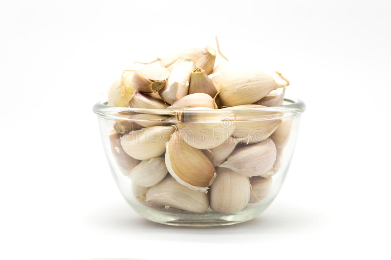 Glass cup of fresh rood garlic, on white. Background royalty free stock image