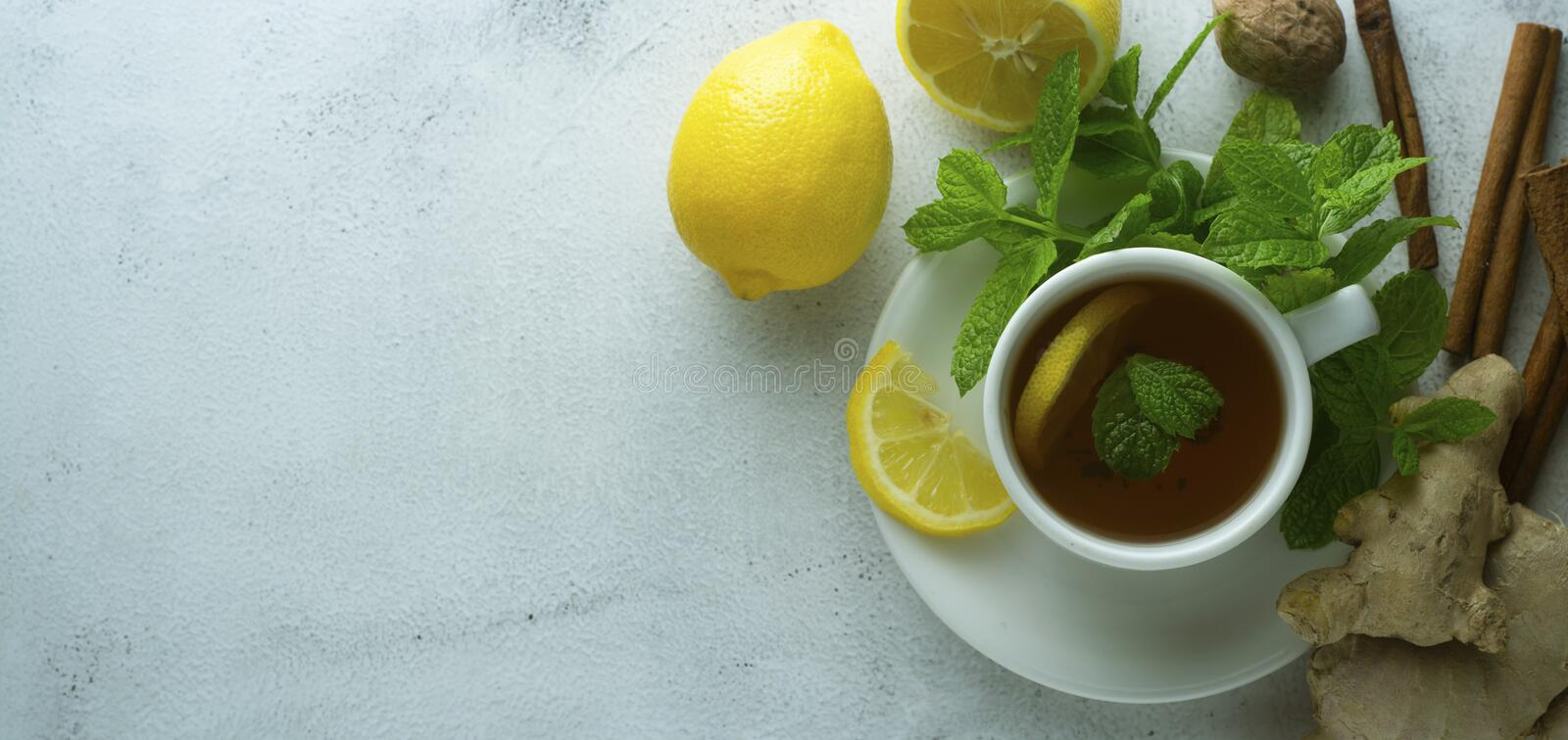 Glass cup of ginger tea with lemons and mint leaves on light background. Ginger tea, drink, cold and autumn time. Banner. Glass cup of ginger tea with lemons and royalty free stock photos