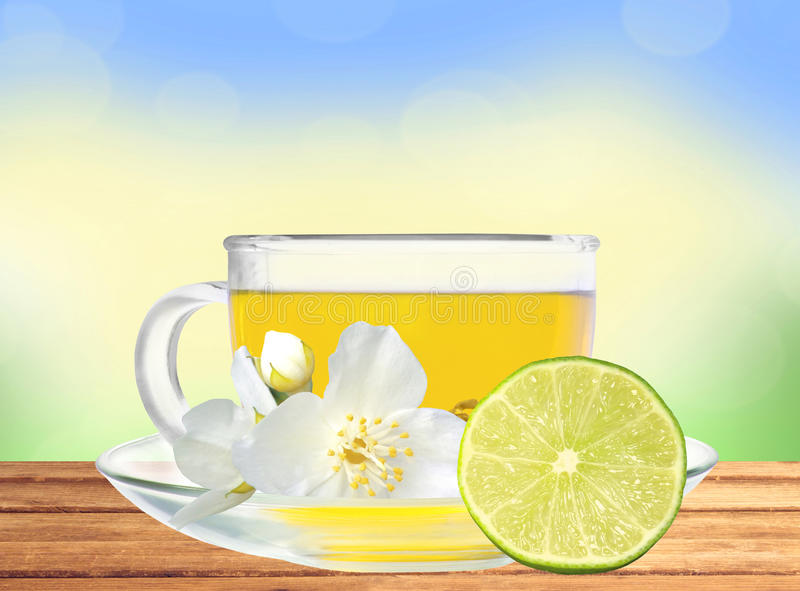 Glass cup of green tea with jasmine flowers and lime on table stock photo