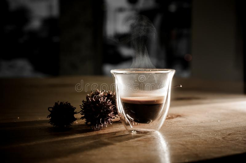 Glass cup of hot coffee with steam from it. Near dried flowers located on the wooden table stock photos