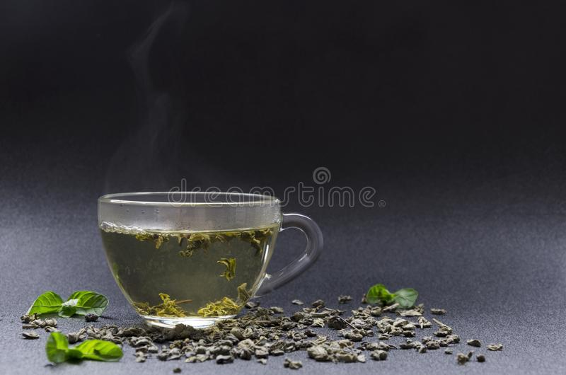 Glass cup of hot green tea, mint leaves on the black background. Closeup of glass cup of hot green tea with mint flavor, dark background Refreshing green tea stock photo