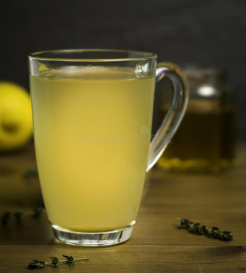 Glass Cup of Hot Lemon, Honey and Ginger Drink with sprigs of Thyme as a cold remedy stock photos