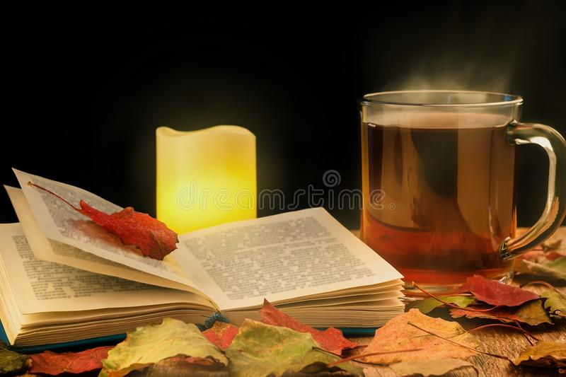 Glass cup of hot tea, glowing candle and opened book on table with autumn leaves. Dark background. Toned royalty free stock photo