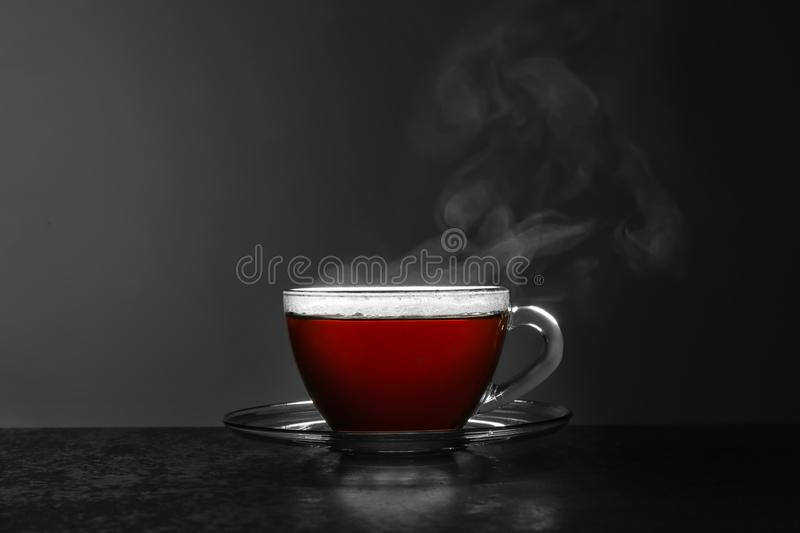 Glass cup of hot tea on stone table against grey background. Space for text royalty free stock photo