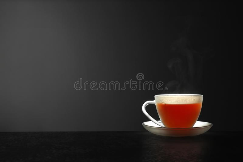 Glass cup of hot tea on stone table against grey background. Space for text stock photo