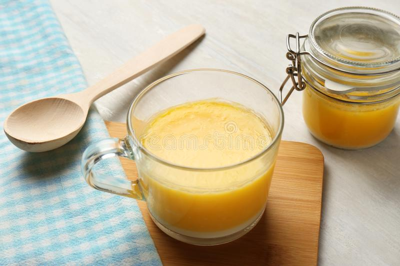 Glass cup and jar with clarified butter. On table royalty free stock photos