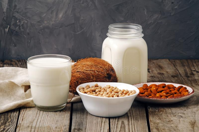 Glass cup and jar of vegan plant milk and almonds, nuts, coconut, soya milk on wooden table. Dairy free milk substitute drinks and royalty free stock photos