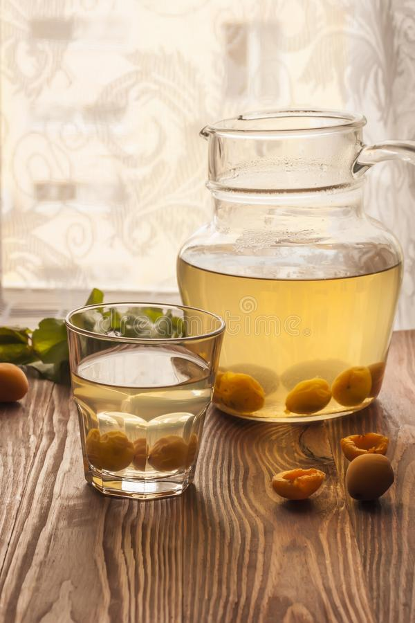 A glass cup and a jug with apricot fruit compote and ripe apricots on a wooden table. Sweet and healthy dessert. Copy space royalty free stock photography