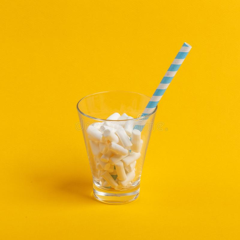 Glass cup with paper tube and marshmallows on a yellow background. Minimalistic concept. Pop summer modern design confectionery still life bright hipster stock photos