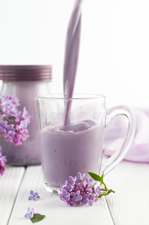 Glass cup with pouring bilberry milkshake near lilac flowers stock photo