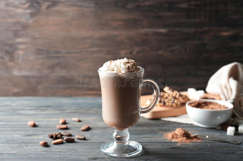 Glass cup of tasty cocoa drink with cream on wooden table stock images