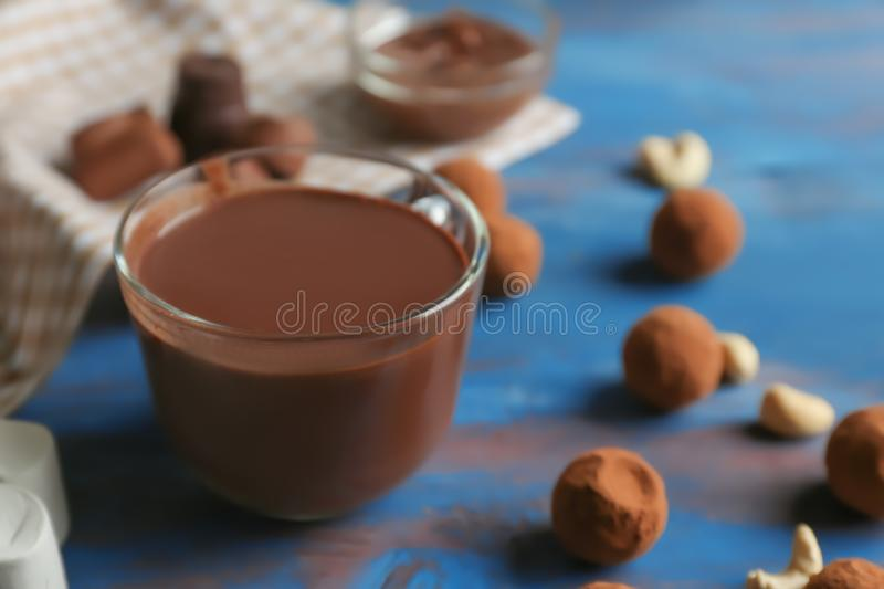 Glass cup of tasty hot chocolate with candies on color wooden background stock photos