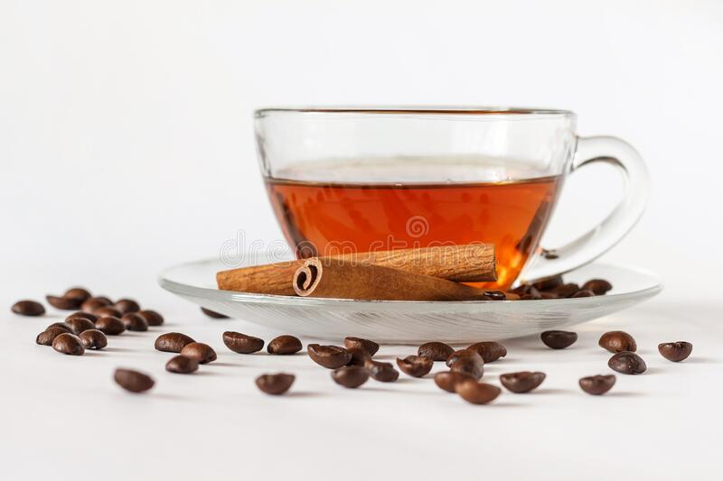 Glass cup of tea with cinnamon sticks and coffee beans. White background. Hot spiced cinnamon tea. Close up stock photography