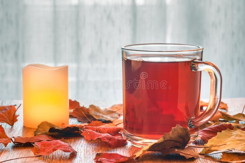 Glass cup of tea and glowing candle on wooden table with autumn leaves. Light tulle background. Glass cup of tea and glowing candle on wooden table with autumn stock photography
