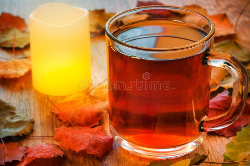 Glass cup of tea and glowing candle on wooden table with autumn leaves. Warm toning. Selective focus royalty free stock image