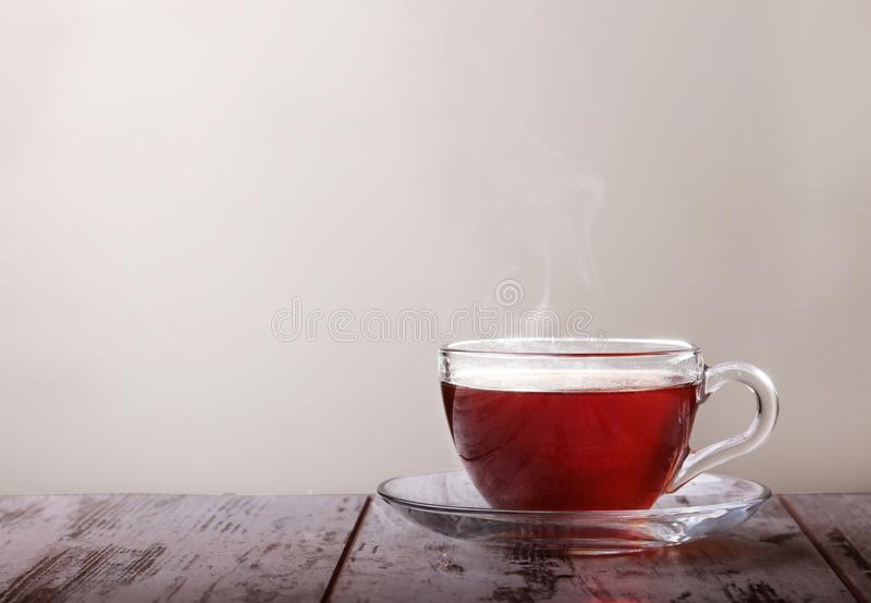 Glass cup with tea and a lemon on a glass saucer stock photo