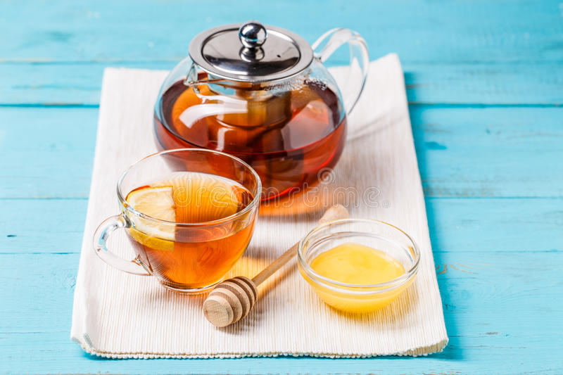 Glass cup of tea with lemon, glass teapot and honey. Glass cup of tea with lemon, glass teapot and honey on blue wooden table royalty free stock photography