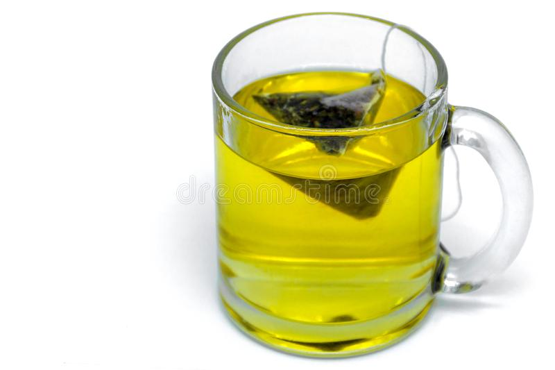Glass cup with teabag, green tea. Isolated on a white stock photography