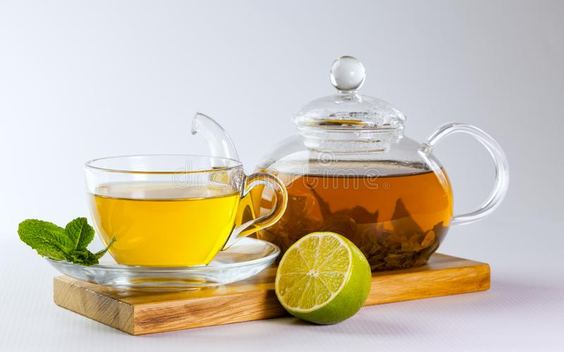 Glass cup and teapot of green tea royalty free stock photography