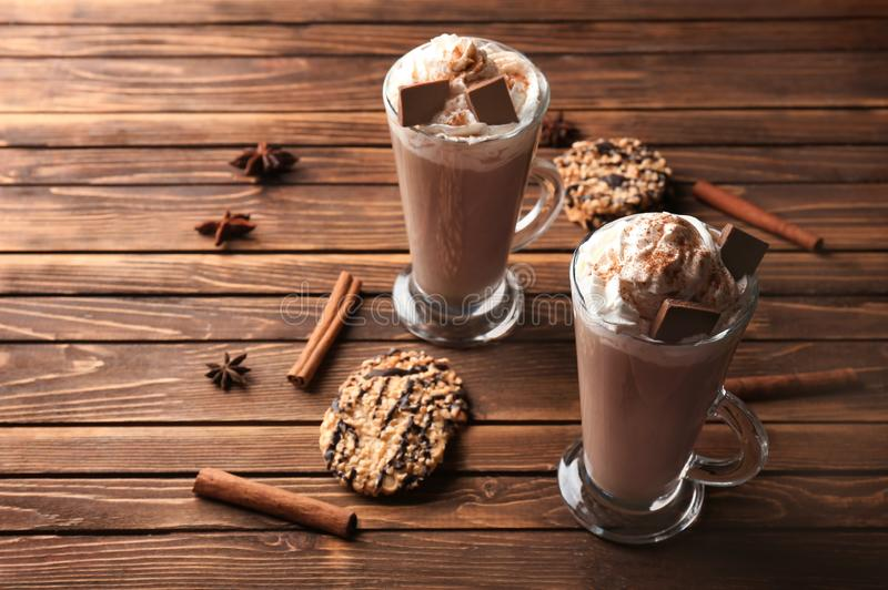 Glass cups of tasty cocoa drink with cream and sweets on wooden table stock image