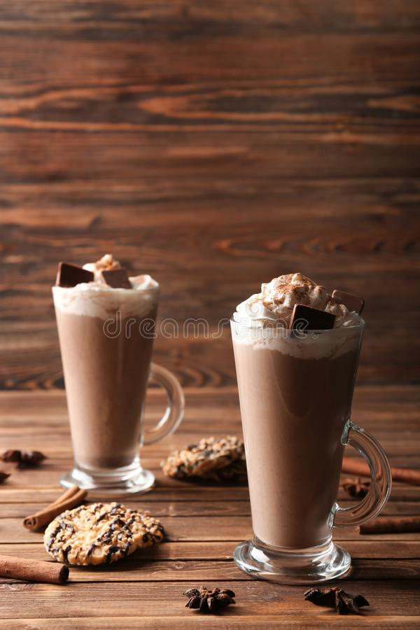Glass cups of tasty cocoa drink with cream and sweets on wooden table stock photos