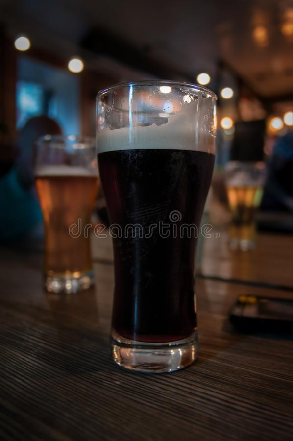 Glass of dark beer. Craft beer with foam stands on dark vintage wooden table in the bar. Brasserie in loft style. stock photos