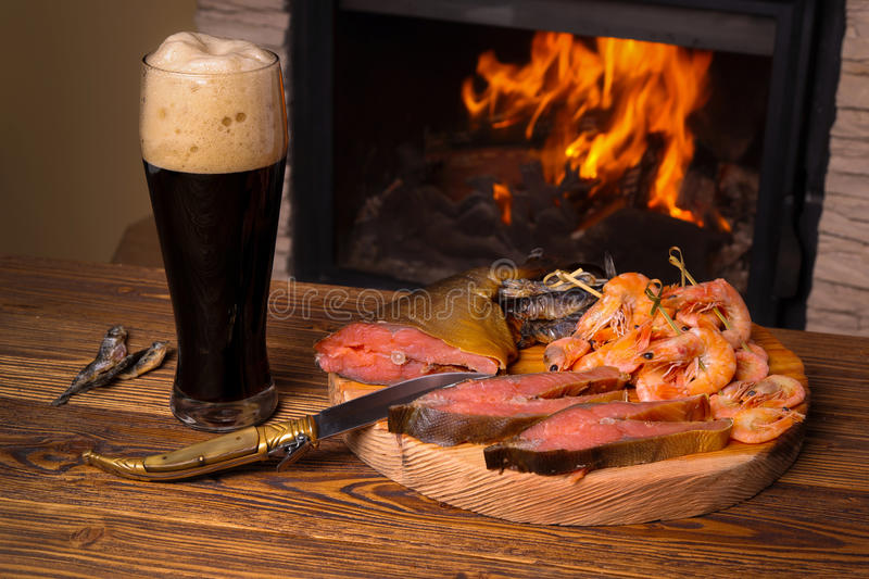 Glass of dark beer and a fish platter on the background of a bur royalty free stock photo