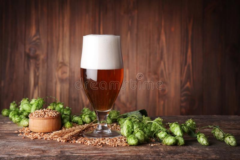 Glass of dark beer and ingredients on table against blurred wooden background stock photo