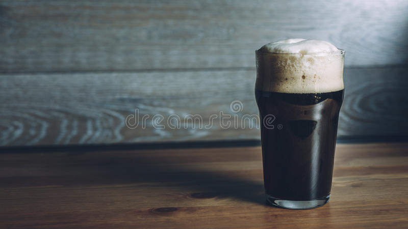Glass of dark beer on wooden surface stock photos