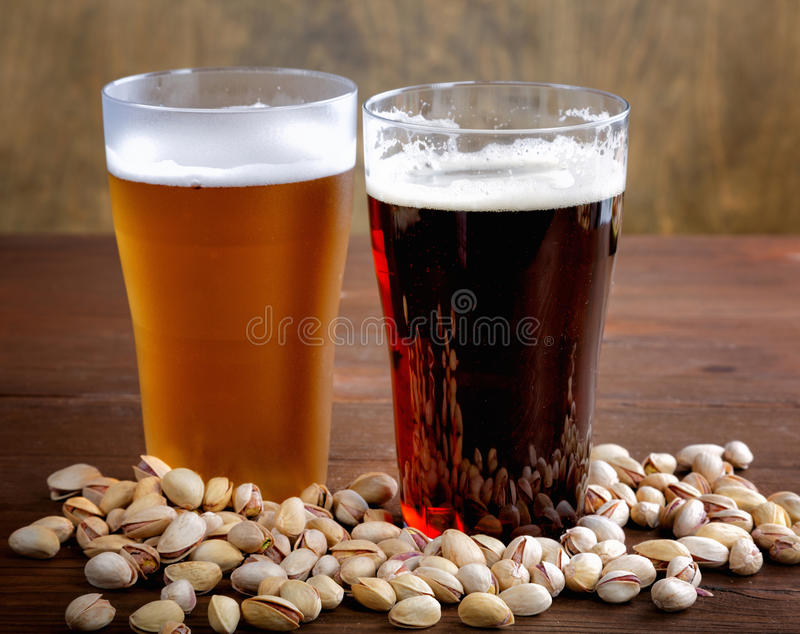 Glass of dark and light beer with nuts. Glass of dark and light beer with salty nuts stock image