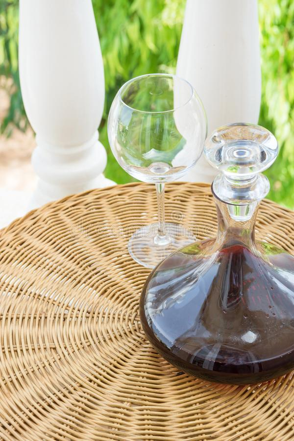 Glass Decanter with Red Wine on Rattan Wicker Table in Garden Terrace of Villa or Mansion. Authentic Lifestyle Image. Gourmet. Glass Decanter with Red Wine on royalty free stock image