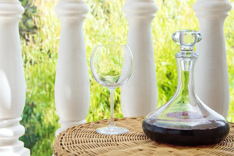 Glass Decanter with Red Wine on Rattan Wicker Table in Garden Terrace of Villa or Mansion. Authentic Lifestyle Image. Relaxation Indulgence Gourmet. Poster stock images