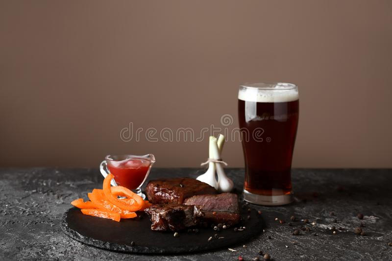 Glass of delicious beer, sliced steak, tomato sauce and vegetables on grunge table stock image