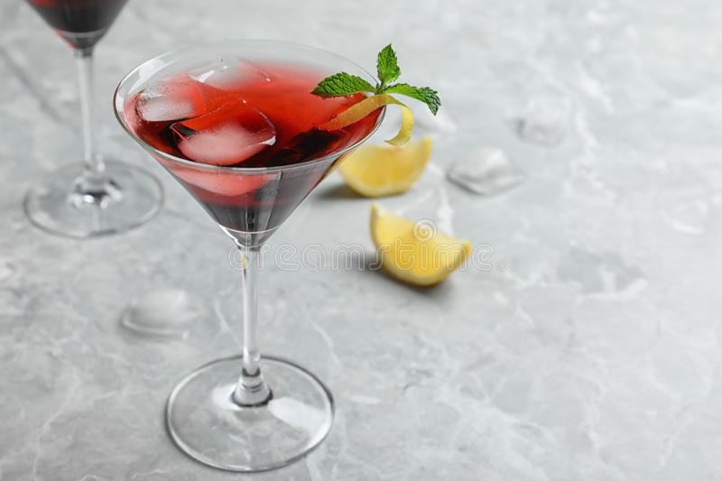 Glass of delicious cocktail with ice on light grey table. Spac. E for text stock photo