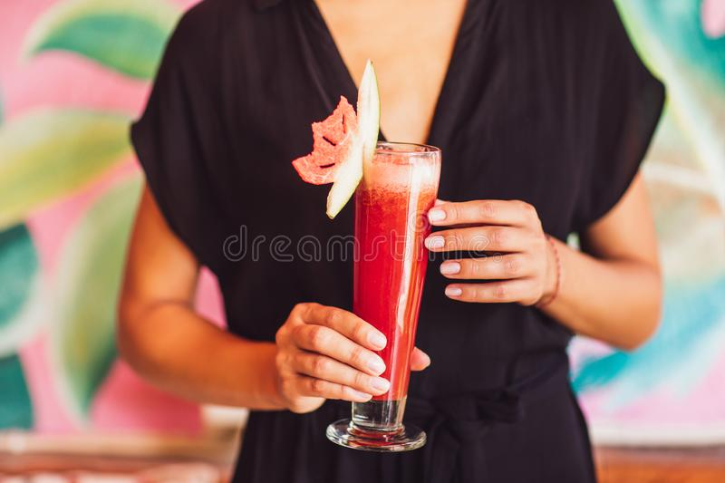 Glass of red watermelon juice in female hands. Glass of delicious healthy watermelon juice in young female hands. Healthy drink concept royalty free stock photo