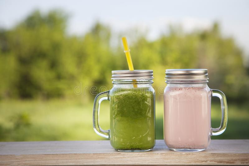 Download Glass Of Detox Smoothie On Wooden Table In The Summer Garden Wit Stock Photo - Image of juice, energy: 117122438