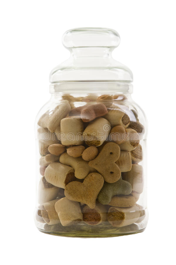 Glass with dog treats. Glass jar filled with various dog treats of different shapes, including hearts and bones, isolated on white stock photography