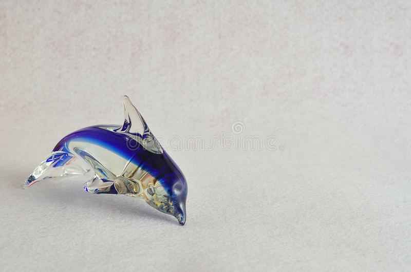 A glass dolphin figurine. That is sold for souvenirs at various gift shops stock images
