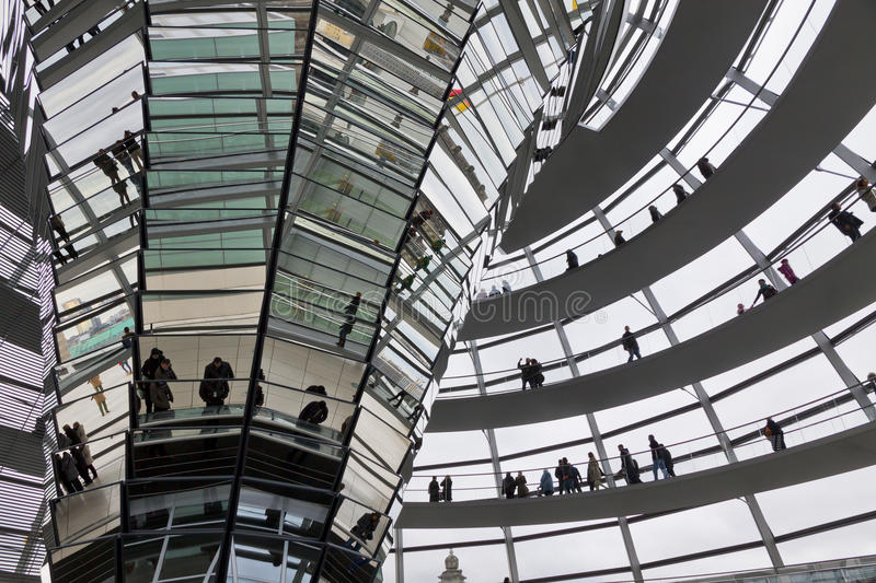 Glass Dome on the top of Reichstag (Bundestag) building. BERLIN, GERMANY - NOVEMBER 10, 2013: People walking inside the Reichstag Dome. It is a glass dome royalty free stock image