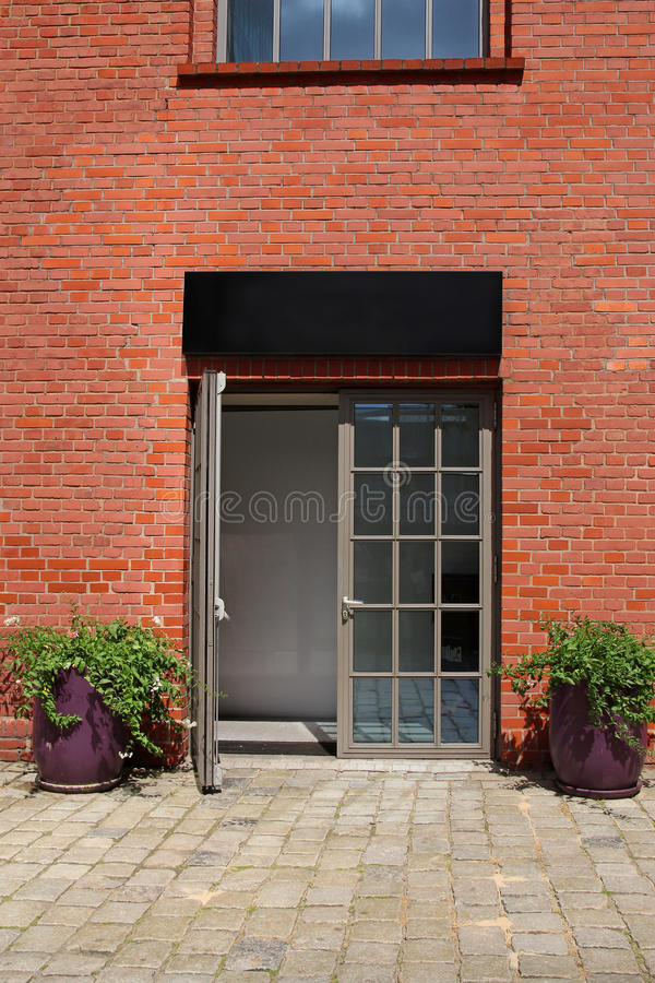 Glass door in brick wall with two flowerpots. Glass door in red brick wall with two flowerpots stock photography