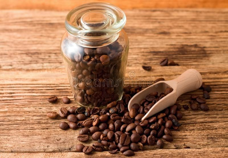 Glass dose full of coffee beans and wooden spoon stock image