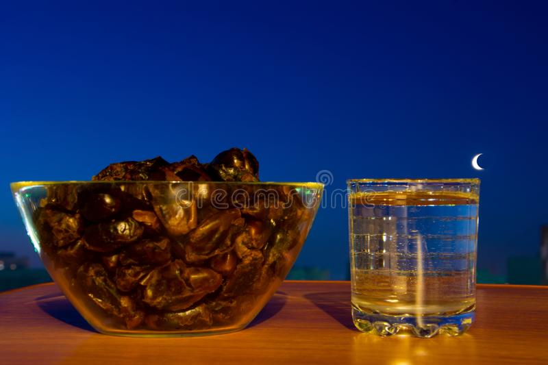Glass of drinking water, dates and moon . Basic food and drink to break Ramadan fast. royalty free stock photography