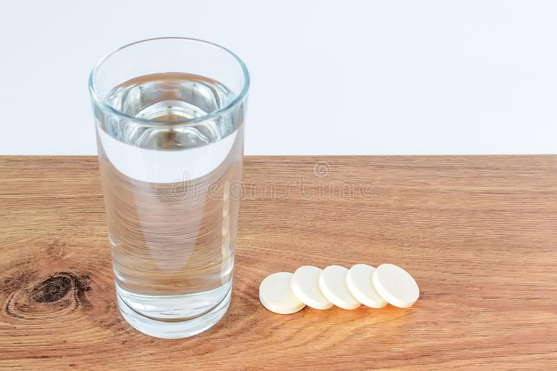 Glass of drinking water and five soluble effervescent vitamin pills on a wooden background with white copy space. Vitamins and. Nutritional supplements. Health stock photo