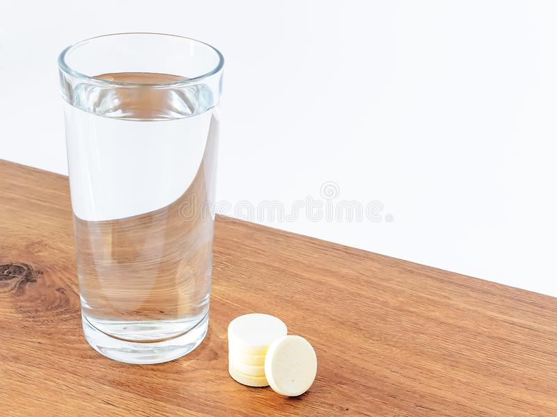 Glass of drinking water and some soluble effervescent vitamin pills on a wooden background with white copy space. Vitamins and. Nutritional supplements. Health royalty free stock photography