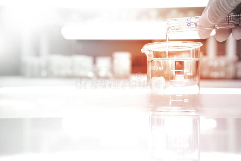 Glass dryckeskärl med vatten och den poring handen av forskaren från cylind arkivfoto